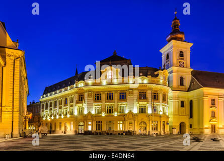Twilight-Bild mit Rathaus und Heilige Dreifaltigkeit die römisch-katholische Kirche in Hermannstadt. Large Square - Stockfoto