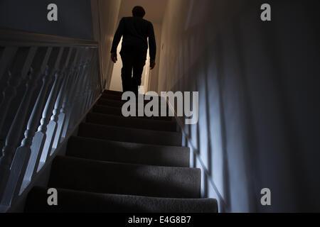 Silhouette eines Mannes zu Fuß nach oben wieder anzuzeigen, Schatten an den Wänden des Lichts unter. - Stockfoto