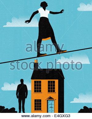 Geschäftsfrau auf Drahtseil über Haus und Mensch - Stockfoto