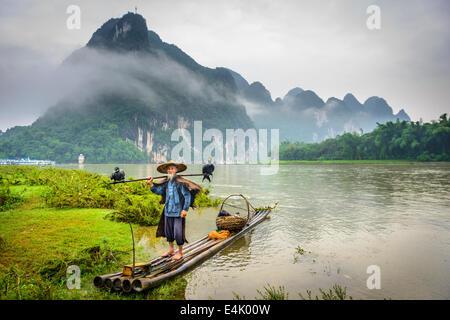 Kormoran Fischer und seine Vögel auf dem Li-Fluss in Yangshuo, Guangxi, China. - Stockfoto