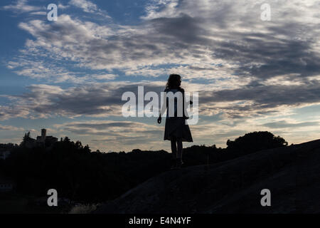 Silhouette einer Frau verloren bei Sonnenuntergang in einem Kleid hält eine Tasche mit Wolken im Hintergrund - Stockfoto