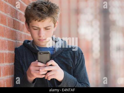 Teenager (16-17) Ziegel Wand SMS gelehnt - Stockfoto