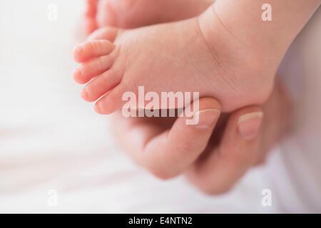 Nahaufnahme von Mutters Hand rührende Baby junge ist (2-5 Monate) Fuß - Stockfoto