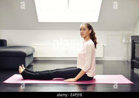 Porträt von Fit junge Frau sitzt auf Gymnastikmatte Blick in die Kamera. Gesunde weibliche Training zu Hause. - Stockfoto