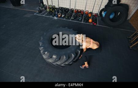 Draufsicht der jungen weiblichen spiegeln schweren Reifen. Frau Crossfit Training im Fitness-Studio zu tun. - Stockfoto