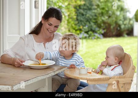 Kleinkind junge (2 Jahre 4 Monate) sitzt auf dem Schoß der Mutter als kleines Mädchen (9 Monate) sitzt im Hochstuhl - Stockfoto