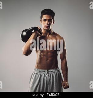Porträt von starken jungen Mann mit Wasserkocher Glocke. Junge muskulöse Kerl mit Crossfit Ausrüstung auf grauem - Stockfoto
