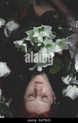 Unschuld, untergetaucht im Wasser mit weißen Rosen, Romantik Szene Teen Stockfoto