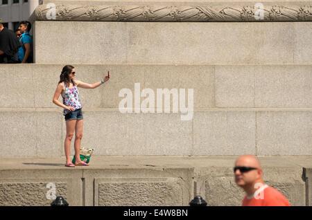 London, England, Vereinigtes Königreich. Junge Frau, die eine Selfie an der Basis der Nelsonsäule, Trafalgar Square - Stockfoto