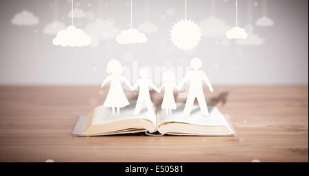 Pappfiguren der Familie auf geöffneten Buch - Stockfoto