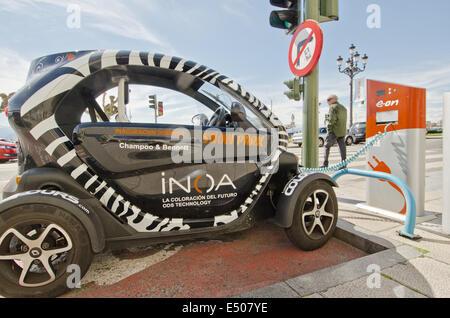 Ein Renault Twizy Elektroauto bekommt seine Batterie aufgeladen an einem E.on Straßenseite Ladestation an der Strandpromenade - Stockfoto