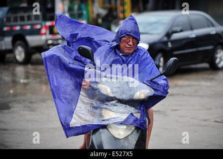 Wenchang, Chinas Provinz Hainan. 18. Juli 2014. Ein Mann trotzt starken Wind als der Taifun Rammasun Ansätze zur - Stockfoto