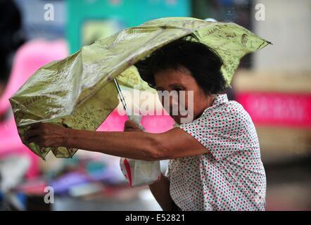 Wenchang, Chinas Provinz Hainan. 18. Juli 2014. Ein Fußgänger Braves starker Wind als der Taifun Rammasun Wenchang, - Stockfoto