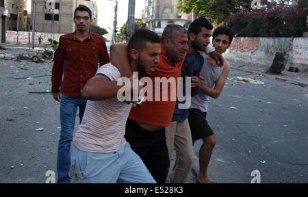 Gaza-Stadt, Palästinensische Autonomiegebiete. 18. Juli 2014. Gaza, Gazastreifen, Palästinensische Gebiete. 18. Juli 2014. Palästinensische Männer helfen einen lokalen Journalist, der bei einem israelischen Luftangriff auf ein Bürogebäude hosting mehrere Medien in Gaza-Stadt, 18. Juli 2014 verletzt habe. Bildnachweis: ZUMA Press, Inc./Alamy Live-Nachrichten