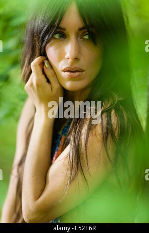 Eine Frau mit langen braunen Haaren draußen im Wald. - Stockfoto