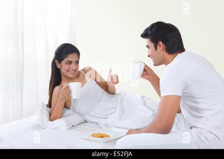 Glückliche junge Frau gestikulieren Daumen nach oben beim Kaffeetrinken mit Mann im Bett - Stockfoto