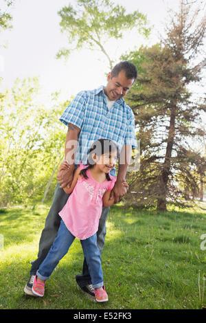 Ein kleines Kind in einem rosa Kleid mit ihren Füßen auf ihres Vaters Füße. - Stockfoto