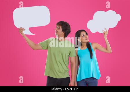 Nachdenklich junges Paar hält Kommunikation Bläschen vor rosa Hintergrund - Stockfoto
