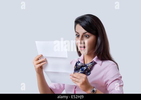 Überrascht Geschäftsfrau lesen Dokument über grauen Hintergrund - Stockfoto