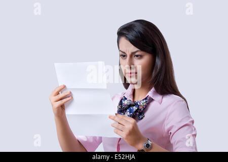 Geschäftsfrau lesen Dokument über grauen Hintergrund - Stockfoto