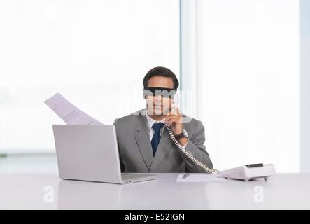 Mit verbundenen Augen Geschäftsmann arbeitet am Schreibtisch im Büro - Stockfoto