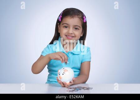 Porträt von netten Mädchen Münzen ins Sparschwein vor blauem Hintergrund - Stockfoto