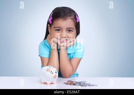 Porträt eines Mädchens mit Münzen und Sparschwein vor blauem Hintergrund - Stockfoto