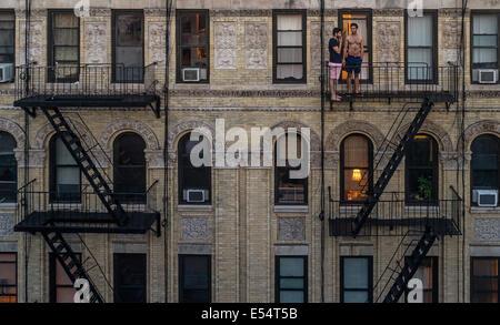 New York, NY 20. Juli 2014 - zwei Männer, die Rauchen von Zigaretten auf der Feuerleiter an einem Sommer Abend © - Stockfoto