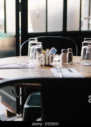 Detail-Aufnahme von Tisch mit Gläsern, Salz- und Pfefferstreuer und Servietten gegen eine mattierte Tür. - Stockfoto