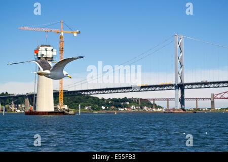 Ein Blick auf die Brücken über den Firth of Forth in Schottland. Die Säule im Vordergrund ist ein Fundament für - Stockfoto