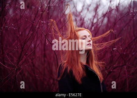 Frau mit langen roten Haaren zwischen Zweigen, Porträt Stockfoto