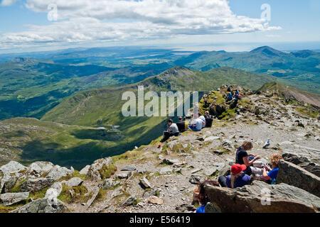 Wanderer nehmen eine Pause, um die Aussicht vom Gipfel des Mount Snowdon. Blick nach Süden über Snowdonia Cardigan - Stockfoto