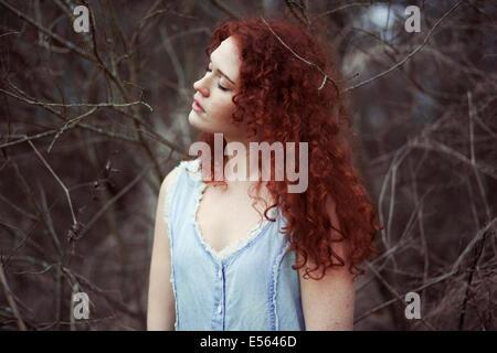 Frau mit langen roten Haaren zwischen Zweigen, Porträt - Stockfoto