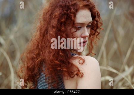 Frau mit langen roten Haaren stehen im Schilf, Porträt - Stockfoto