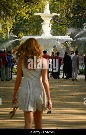 Rückansicht einer jungen weißen Frau mit langen Haaren in einem Sommerkleid, nähert sich die Menschenmenge in Forsyth - Stockfoto