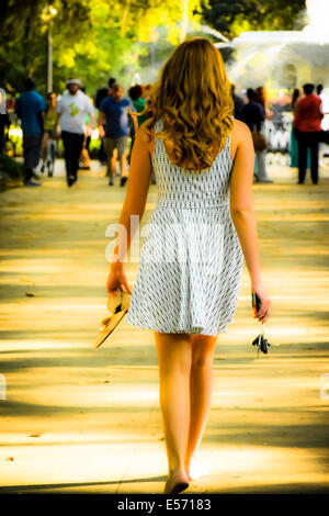 Rückansicht einer jungen weißen Frau mit langen Haaren, die barfuß in einem Sommerkleid in Richtung Forsyth Park - Stockfoto