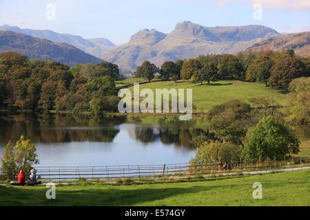 Walkers ruhen neben Loughrigg Tarn im englischen Lake District mit Langdale Pikes im Hintergrund - Stockfoto