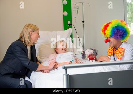 Männlichen Arzt mit Clown Kostüm machen Mädchen geduldig Lächeln im Krankenhausbett - Stockfoto