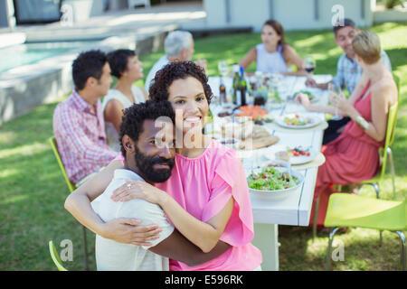 Paar umarmt am Tisch im freien - Stockfoto