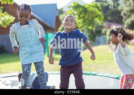 Kinder springen auf dem Trampolin im freien - Stockfoto