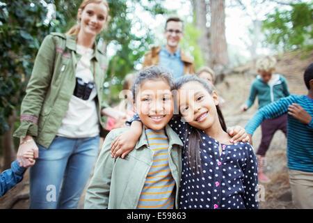 Schüler und Lehrer lächelnd in Wald Stockfoto