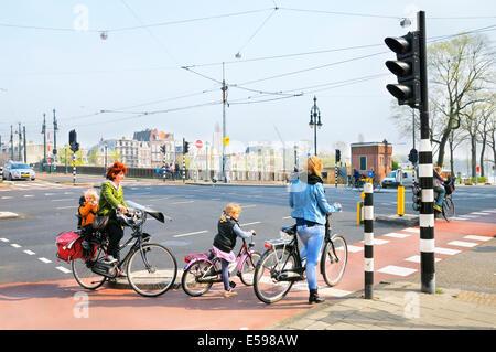 Frauen und Kinder auf Fahrrädern warten an einer Straßenkreuzung, Amsterdam, Niederlande - Stockfoto