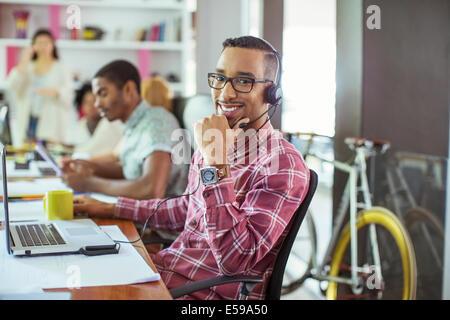 Mann lächelnd am Schreibtisch im Büro - Stockfoto