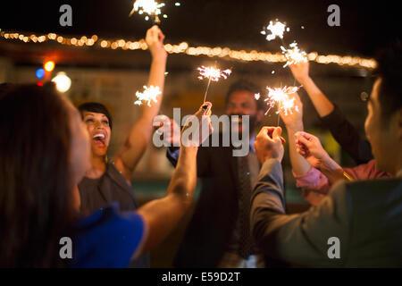 Freunde mit Wunderkerzen auf Party Spielen - Stockfoto