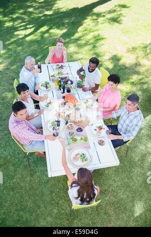 Freunde, die gemeinsam am Tisch im Freien essen Stockfoto