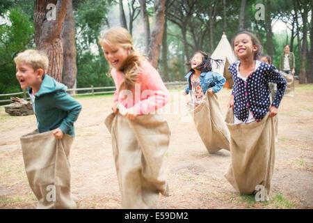 Kinder mit Sackhüpfen im Feld - Stockfoto
