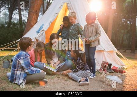 Lehrer und Schüler lesen auf Campingplatz - Stockfoto