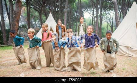 Kinder mit Sackhüpfen auf Campingplatz - Stockfoto