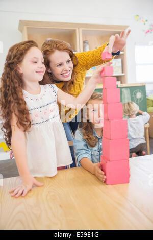 Schüler und Lehrer Stapelblöcke im Klassenzimmer - Stockfoto