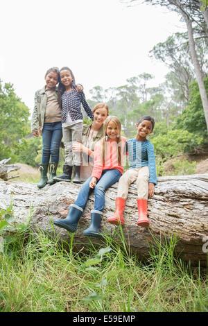 Schüler und Lehrer lächelnd auf Holzscheit - Stockfoto